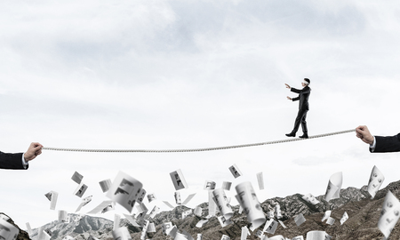 Businessman walking blindfolded on rope among flying documents and above high mountains as symbol of hidden threats and support. Nature view on background. Фото со стока