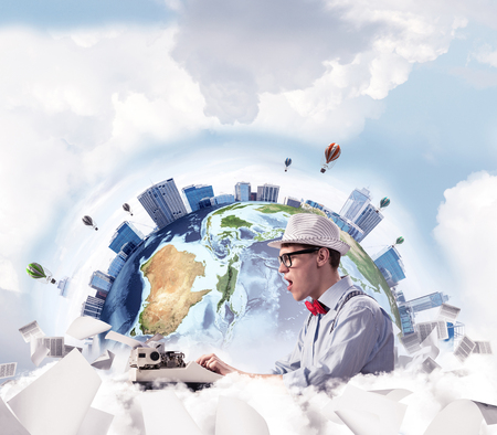 Emotional young man writer in hat and eyeglasses feeling surprised while using typing machine at the table with flying papers and Earth globe among cloudy skyscape on background.