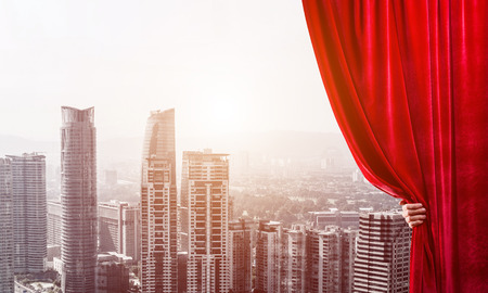 Hand of businessman opening red velvet curtain and cityscape at background Stock Photo - 118958479