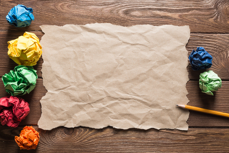 Crumpled brown paper sheet and pencil on wooden table Stock Photo - 119021233