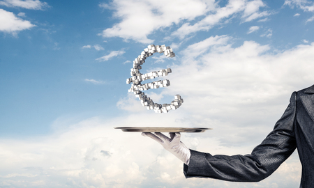 Cropped image of waitresss hand in white glove presenting multiple cubes in form of euro sign on metal tray with cloudy skyscape on background.