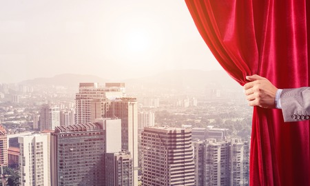 Hand of businessman opening red velvet curtain and cityscape at background Stock Photo - 119020972
