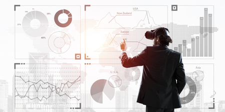 Young businessman in virtual helmet using media panel. Mixed media