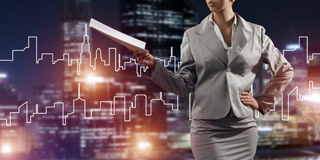 Close view of businesswoman against modern cityscape holding papers in hand Stock Photo