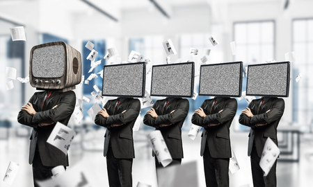 Businessmen in suits with TV instead of their heads keeping arms crossed while standing in a row and one at the head with old TV inside office building.