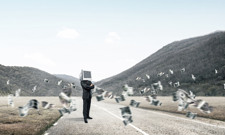 Businessman in suit with monitor instead of head keeping arms crossed while standing on the road among flying dollar banknotes with beautiful landscape on background. Stock Photo