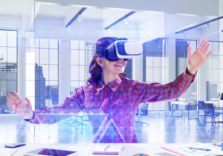 Conceptual image of young and beautiful woman in checkered shirt using virtual reality headset and interracting with media interface while sitting inside bright office building. Stock Photo - 119094539