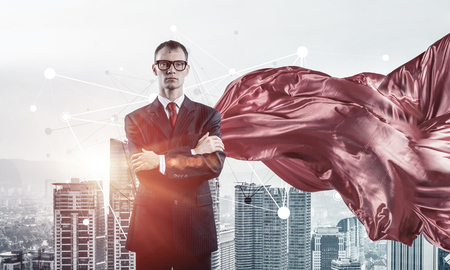Young confident businessman wearing red cape against modern city background Stock Photo