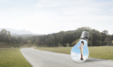 Young businesswoman trapped inside of light bulb on asphalt road 版權商用圖片