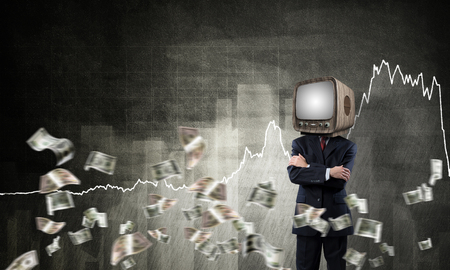 Businessman in suit with old TV instead of head keeping arms crossed while standing against flying dollars and analytical charts drawn on wall on background. 3D rendering.