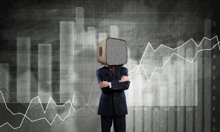 Businessman in suit with old TV instead of head keeping arms crossed while standing against analytical charts drawn on wall on background.