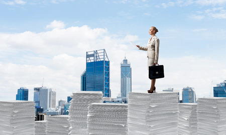 Confident business woman in suit standing on pile of documents with cityscape on background. Mixed media.