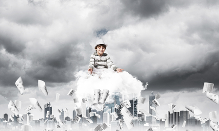 Young little boy keeping eyes closed and looking concentrated while meditating on cloud among flying papers with cityscape view on background.