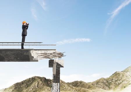 Young engineer in suit and helmet looking in binoculars while standing on broken bridge with skyscape on background. 3D rendering.