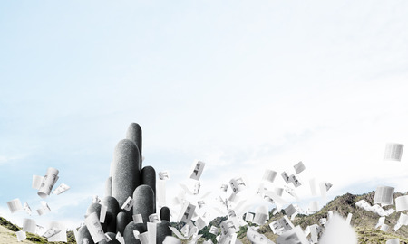 Image of high and huge stone columns located outdoors among flying papers with beautiful landscape on background. Wallpaper, backdrop with copyspace.