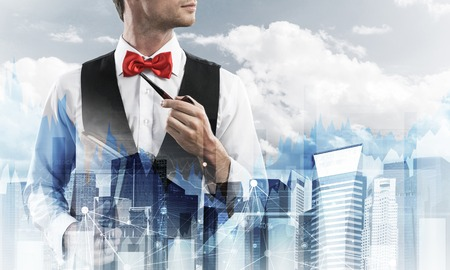 Double exposure of confident and young businessman in smart-casual wear smoking pipe and modern cityscape with business and media interface. Concept of new technologies for modern business. Stock Photo