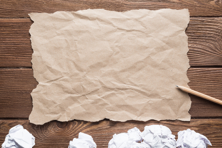 Crumpled brown paper sheet and pencil on wooden table Stock Photo - 119124520