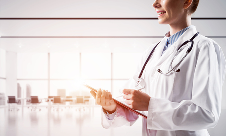Cropped image of young and successful female medical industry employee standing inside modern clinic building with sunlight on background. Medical industry concept Stock Photo