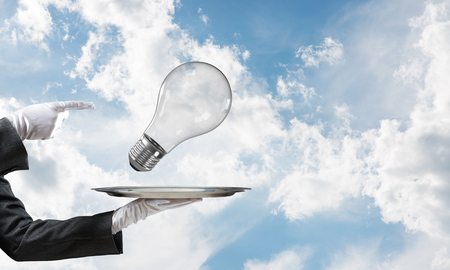 Cropped image of waitresss hand in white glove presenting lightbulb on metal tray and pointing on it as symbol of new idea with cloudy skyscape on background.