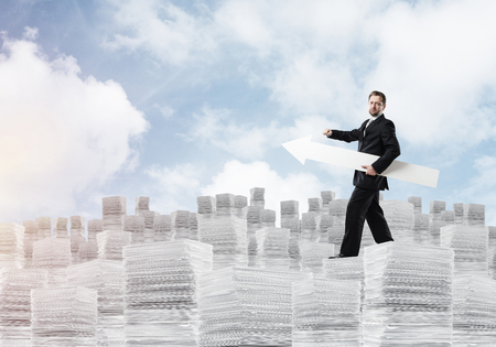 Successful development of new startup project by means of big white arrow in businessmans hand standing on columns of documents with cloudy skyscape view on background. Stock Photo