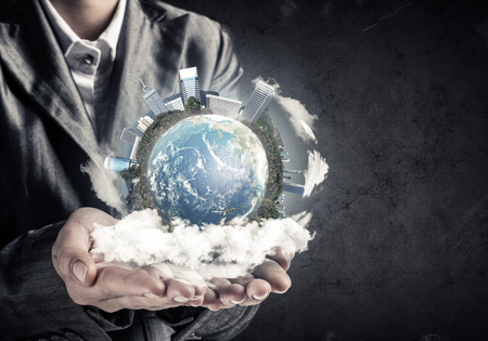 Closeup of businessman in suit keeping in hands Earth globe with buildings, gray wall on background. Elements of this image are furnished by NASA.
