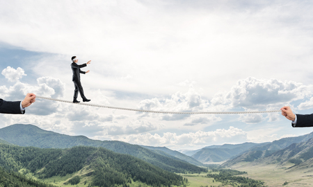 Businessman walking blindfolded on rope above high mountains as symbol of hidden threats and support. Skyscape and nature view on background. Stock Photo