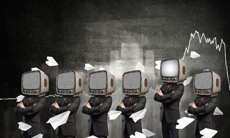 Businessmen in suits with old TV instead of their heads keeping arms crossed while standing among flying paper planes and against analytical charts drawn on wall on background.