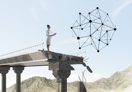 Female doctor in white medical suit looking at social network structure while standing at the end of broken bridge. Medical industry concept. Landscape view on background Stock Photo