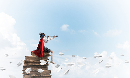 Little child in mask and cape floating on pile of books and looking in spyglass