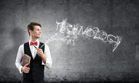 Horizontal shot of confident and young businessman in smart-casual wear smoking pipe while standing against gray dark wall and technology word made from smoke on background.