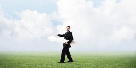 Confident businessman holding white big arrow in his hand while standing at green meadow with cloudy skyscape view on background Stock Photo
