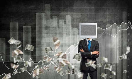 Businessman in suit with monitor instead of head keeping arms crossed while standing against flying dollars and analytical charts drawn on wall on background. 3D rendering. Stock Photo