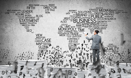 Businessman in suit standing among flying letters with speaker in hand with business-related terms in form of world map on background. Mixed media. Stock Photo