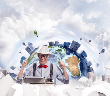 Cheerful young man writer in hat and eyeglasses looking happy while sitting with typing machine at the table with flying papers and Earth globe among cloudy skyscape on background. Elements of this image furnished by NASA