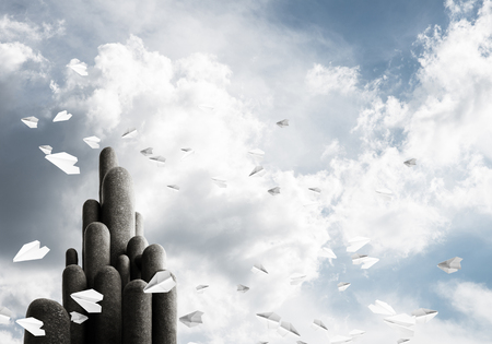 Image of high and huge stone columns located outdoors among flying paper planes with beautiful landscape on background. Wallpaper, backdrop with copyspace. Stock Photo