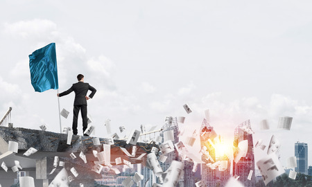 Rear view of confident businessman in suit holding flag in hand while standing among flying papers on broken bridge with cityscape and sunlight on background. 3D rendering. Stock Photo