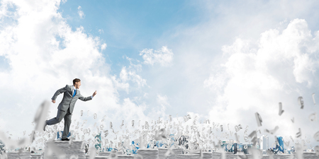 Businessman in suit running with phone in hand among flying letters with cloudly sky on background. Mixed media.