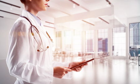 Side view of young female medical industry employee holding tablet in hands while standing inside bright hospital building. Medical industry concept Stock Photo