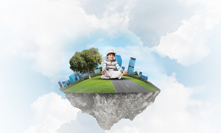 Young little boy keeping eyes closed and looking concentrated while meditating on flying island in the air with cloudy skyscape on background. 3D rendering.