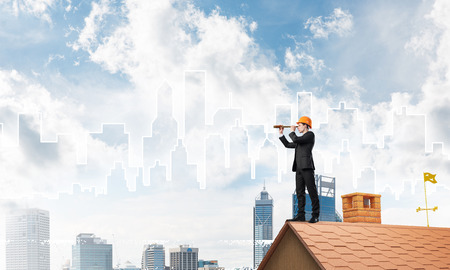 Young businessman in suit and helmet on roof edge. Mixed media Stock Photo