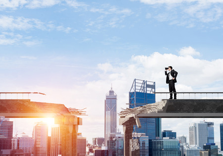 Businessman in suit looking in binoculars while standing on broken bridge with cityscape and sunlight on background. 3D rendering.