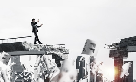 Businessman walking blindfolded among flying documents on concrete bridge with huge gap as symbol of hidden threats and risks. Cityscape and sunlight on background. 3D rendering. Standard-Bild
