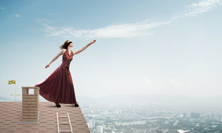 Young attractive woman on brick house roof stretching hand to sky. Mixed media