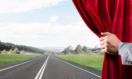 Human hand opens red velvet curtain to landscape with road Stock Photo - 119255157
