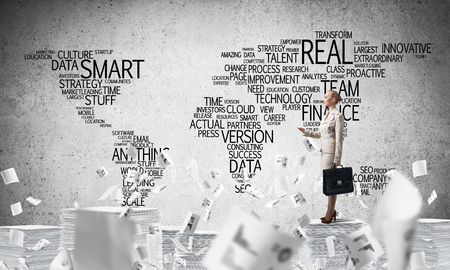 Business woman in suit standing among flying documents with business-related terms in form of world map on background. Mixed media. Stock Photo