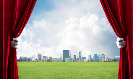 Human hand in glove opens red velvet curtain to cityscape and green meadow Stock Photo - 119215883