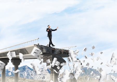 Businessman walking blindfolded among flying documents on concrete bridge with huge gap as symbol of hidden threats and risks. Skyscape and nature view on background. 3D rendering. Standard-Bild