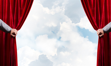 Human hand opens red velvet curtain on blue sky background Stock Photo - 119324708