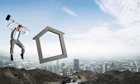 Jumping businessman crashing big house symbol with city view on background. 3D rendering. Imagens