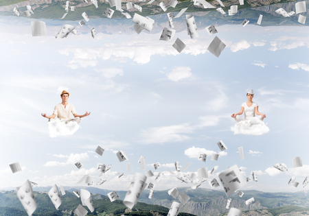 Young couple keeping eyes closed and looking concentrated while meditating on clouds among flying papers and between two nature worlds.